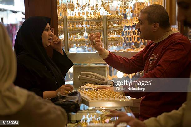 The owner of a gold shop Muhammed Aziz right bargains with Amal Muhammed left about the price of a gold necklace on February 28 2007 in Kadhimiya...
