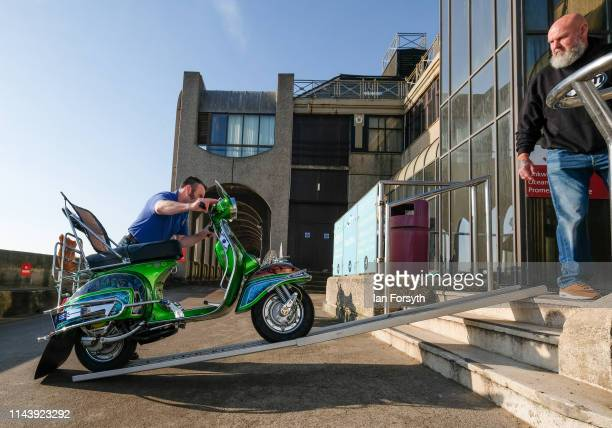 The owner of a scooter pushes it up a ramp into the Spa building as scooter enthusiasts from all around the country arrive to take part in the first...