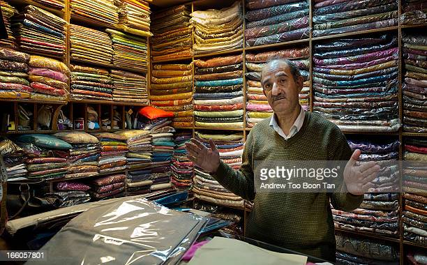 The owner of a small pashmina shop in New Delhi explains to potential buyers the fine points about the quality of the fabric.
