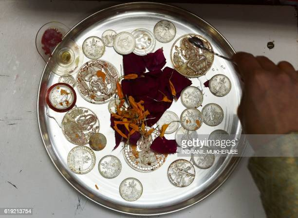 The owner of an Indian brokerage house offers a puja by sprinkling holy water onto ancestral coins before the start of Muhurat Trading a special...