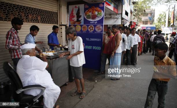 The owner of MM Mithaiwala distributes free vada pav during the hours of nationwide Bandh near the station at Malad in Mumbai India