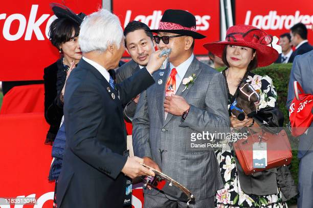 The owner of racehorse Lys Gracieux, Hiroaki Akita wipes sweat from the face of trainer Yoshito Yahagi after winning race 9 the Ladbrokes Cox Plate...