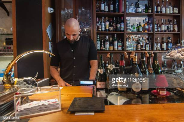 The owner of the Antonio Ferrari restaurant makes a bill on February 15, 2017 in Padova, Italy. The restaurant offers a 5% discount off the total...