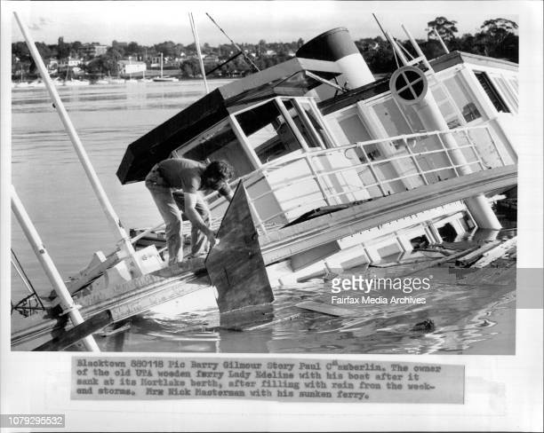 The owner of the old UTA wooden ferry Lady Edeline with his boat after it sank at its Mortlake berth after filling with rain from the weekend storms...