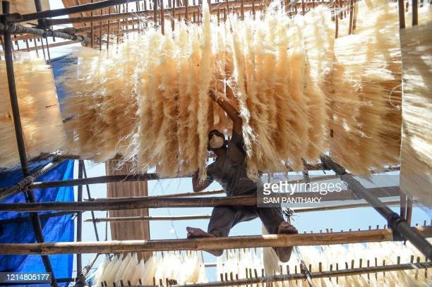 The owner of the workshop, Jamilbhai Ansari, wearing a facemask and hand gloves dries vermicelli in Ahmedabad on May 23, 2020.