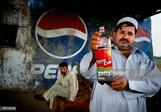 The owner of this restaurant of fresh fish ' Adi Za ' drinks and shows a MeccaCola bottle on July 2004 in Afghanistan