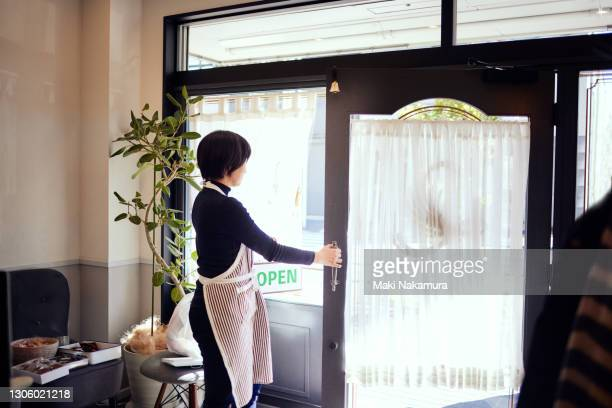 the owner who hangs an open sign on the door at an aesthetic salon. - store opening stock pictures, royalty-free photos & images