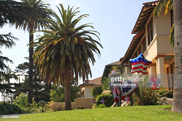The owners of this home in Santa Barbara California dressed up the permanent dog statue on their front lawn in American flag attire and decor for the...