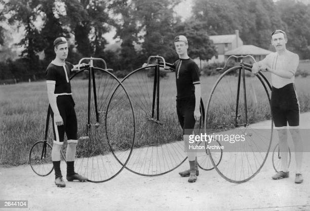 The owners of three penny farthing bicycles stand proudly with their machines