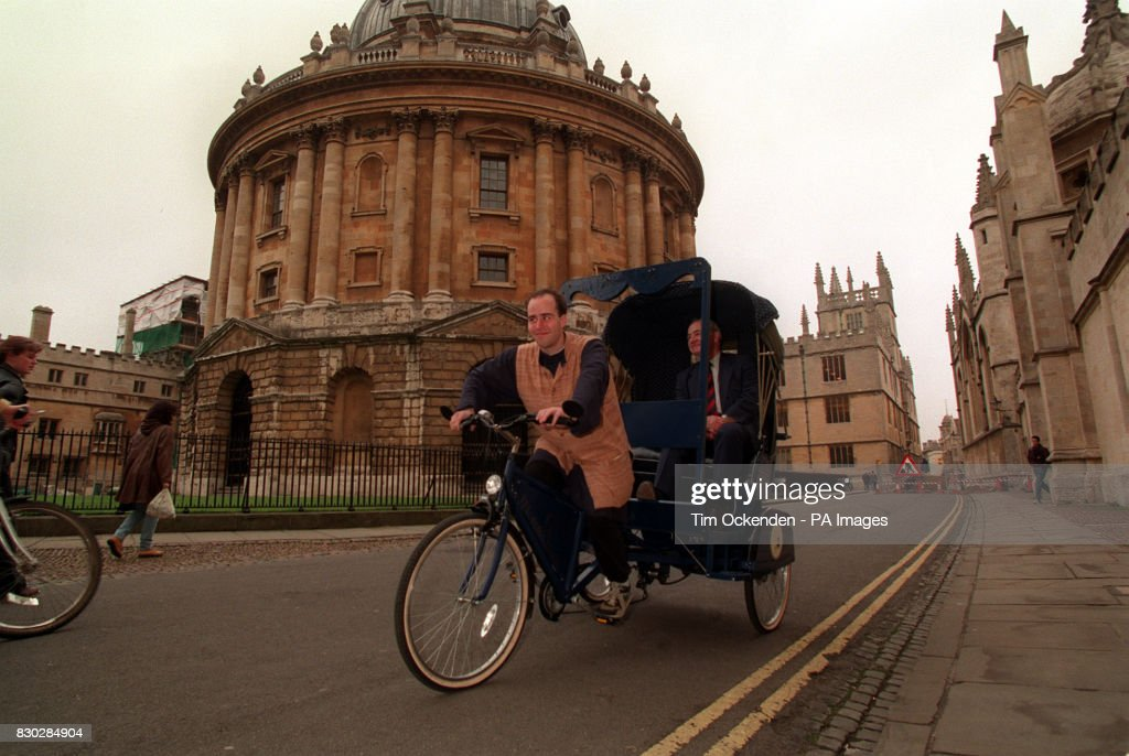 The Oxford Rickshaw Service carries Colin Dexter (creator of Inspector Morse)along Catte Street in Oxford. Pedal power is provided by student Tom Ziessel. The buildings in the background are (l-r) Brasenose College, the Radcliffe Camera (a library), the Bodleian library, the Codrington library and part of All Souls' College. * In the background (l-r) can be seen Brasenose College, The Radcliffe Camera (a library), the Bodleian Library, the Codrington and part of the wall of All Soul's College.