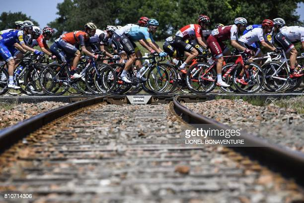 TOPSHOT The pack cross rail tracks during the 1875 km eighth stage of the 104th edition of the Tour de France cycling race on July 8 2017 between...