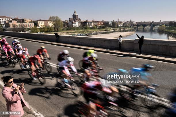 TOPSHOT The pack of riders crosses the Ticino river in Pavia with the 14th 15th Century Pavia Monastery in background during the oneday classic...