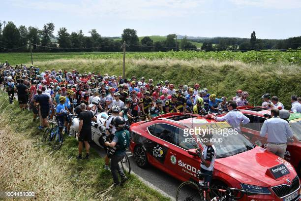 The pack of riders waits for the stage to resume after tear gas was used during a farmers' protest who attempted to block the stage's route during...