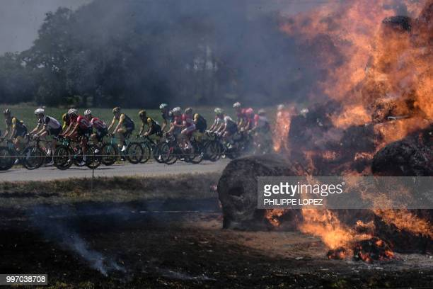 The pack pedals past haystacks that caught fire accidentally during the sixth stage of the 105th edition of the Tour de France cycling race between...