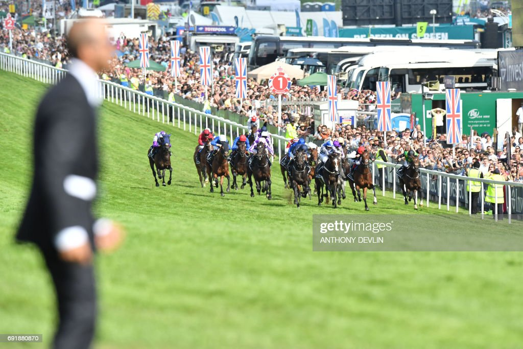 TOPSHOT - The pack race the final furlongs in the Epsom Derby on the second day of the Epsom Derby Festival in Surrey, southern England on June 3, 2017. / AFP PHOTO / Anthony Devlin