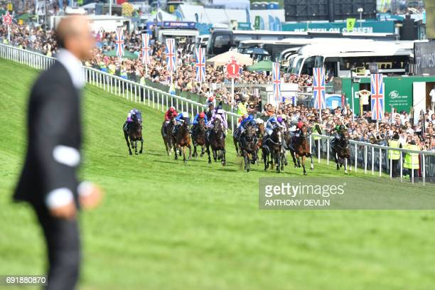 The pack race the final furlongs in the Epsom Derby on the second day of the Epsom Derby Festival in Surrey, southern England on June 3, 2017. / AFP...