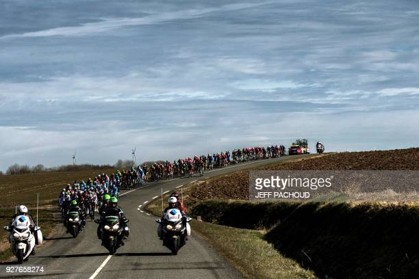TOPSHOT The pack rides along a curved road through the countryside during the second stage of the Paris Nice cycling race between Orsonville and...