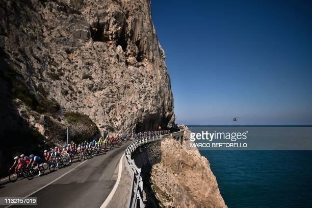 The pack rides along Cape Noli during the oneday classic cycling race Milan San Remo on March 23 2019