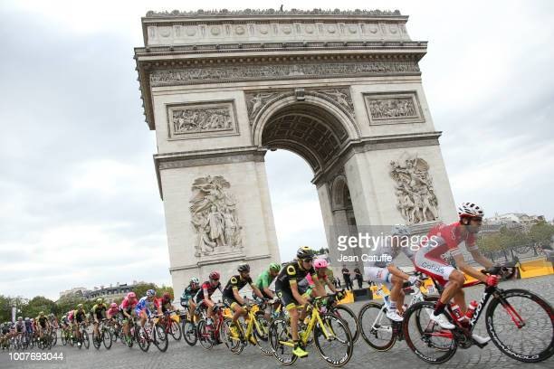 The pack rides around the Arc de Triomphe during stage 21 of Le Tour de France 2018 between Houilles and Paris - avenue des Champs-Elysees on July...