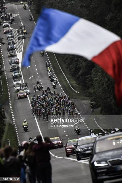 The pack rides as a supporter waves a French national flag during the 2145 km twelfth stage of the 104th edition of the Tour de France cycling race...
