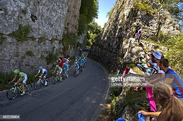 The pack rides during the 1875 km eleventh stage of the 101st edition of the Tour de France cycling race on July 16 2014 between Besancon and Oyonnax...