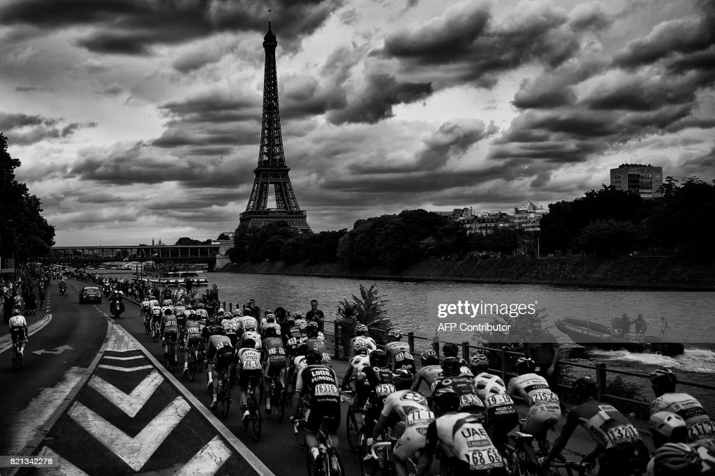 The pack rides in front of the Eiffel Tower and the Seine river during the 103 km twenty-first and last stage of the 104th edition of the Tour de France cycling race on July 23, 2017 between Montgeron and Paris Champs-Elysees. /