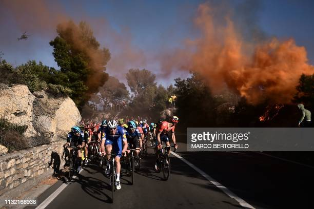 TOPSHOT The pack rides in the ascent of Capo Berta during the oneday classic cycling race Milan San Remo on March 23 2019