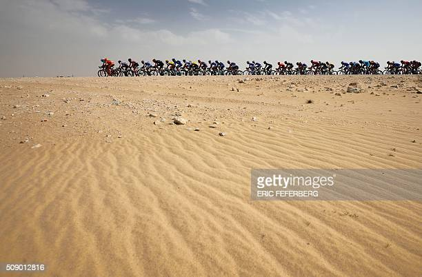 The pack rides in the desert during the first stage of the 2016 Tour of Qatar, between Dukhan and Al Khor Corniche on February 8, 2016. Britain's...