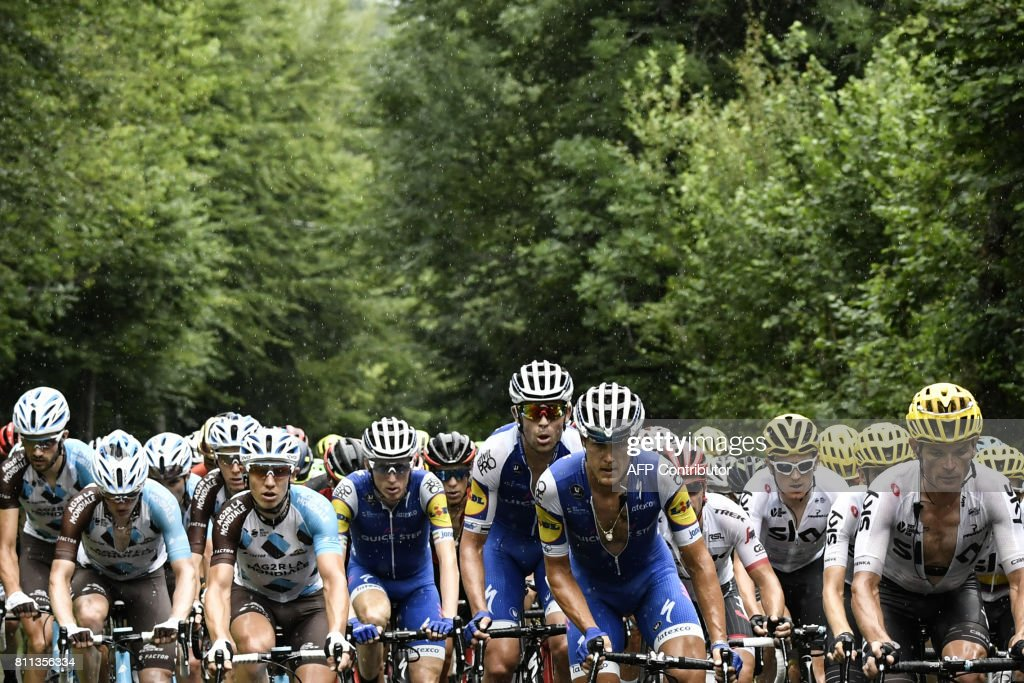 The pack rides in the rain during the 181,5 km ninth stage of the 104th edition of the Tour de France cycling race on July 9, 2017 between Nantua and Chambery. /