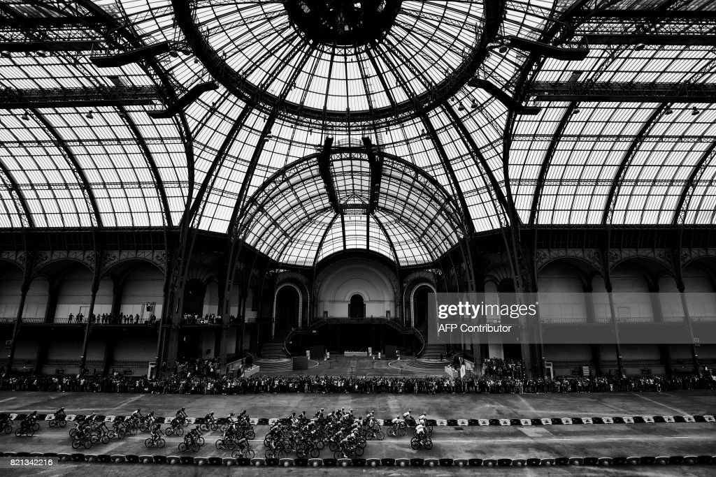 The pack rides inside the Grand Palais in Paris during the 103 km twenty-first and last stage of the 104th edition of the Tour de France cycling race on July 23, 2017, between Montgeron and Paris Champs-Elysees. /