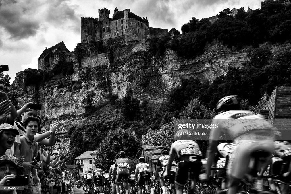 The pack rides near the Beynac castle as fans cheer during the 178 km tenth stage of the 104th edition of the Tour de France cycling race on July 11, 2017 between Perigueux and Bergerac. /