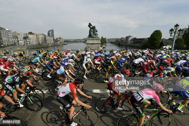The pack rides on a bridge in Liege on April 22, 2018 at the beginning of the 104th edition of the Liege-Bastogne-Liege one day cycling race, the...