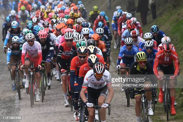 The pack rides on the Briastre to Viesly cobbled sector during the 117th edition of the ParisRoubaix oneday classic cycling race between Compiegne...
