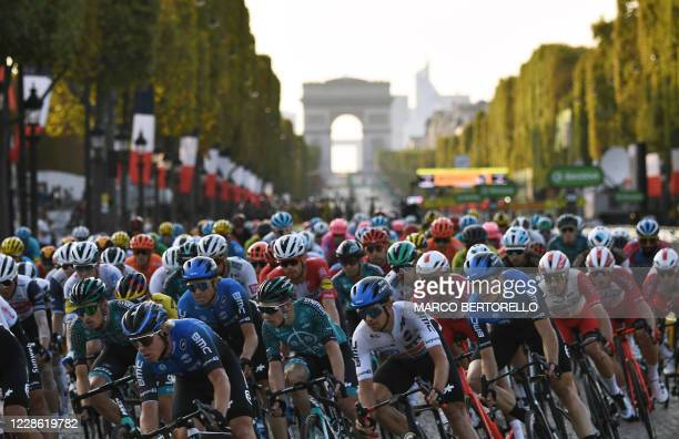 The pack rides on the Champs Elysees avenue with the Arc de Triomphe in the background during the 21st and last stage of the 107th edition of the...
