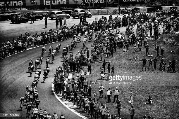 The pack rides on the Circuit de SpaFrancorchamps motorracing circuit as supporters cheer during the 2125 km third stage of the 104th edition of the...