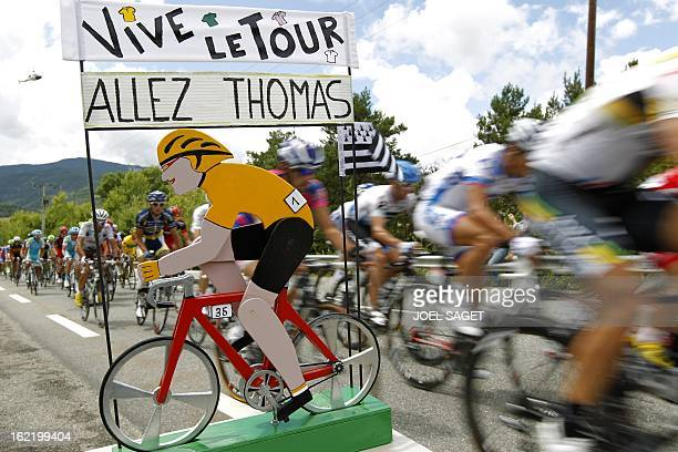 The pack rides past a cycling decoration supporting Yellow jersey of overall leader France's Thomas Voeckler during the 1625 km and sixteenth stage...