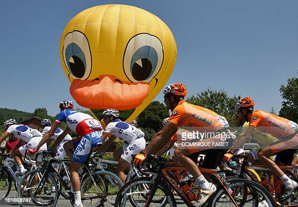 The pack rides past a giant balloon representing Tweety bird cartoon character during the 18th stage of the 94th Tour de France cycling race between...