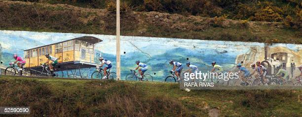 The pack rides past a mural painting in La Arboleda during the second stage of the Tour of the Basque Country - Vuelta al Pais Vasco cycling race, 05...