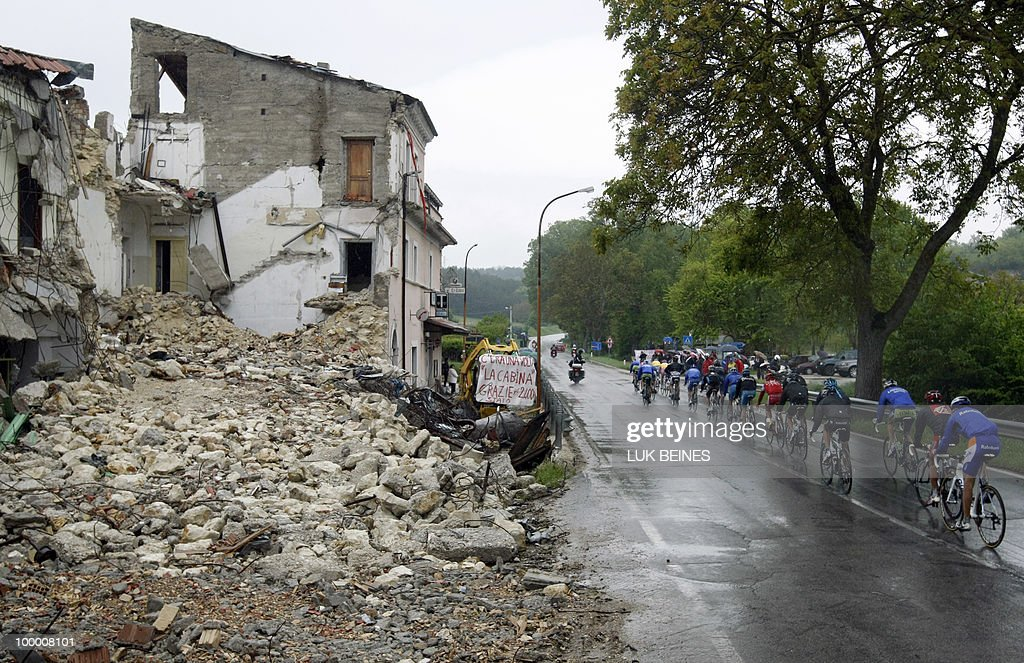 The pack rides past a village hit by an eartquake in 2009 during the11 st stage of the 93rd Giro d'Italia going from Lucera to L'Aquila on May 19, 2010 in L'Aquila. Australian Richie Porte (Saxo Bank) takes the lead of the race while Russia's Evgeny Petrov (Katusha) won the stage. AFP PHOTO/Luk Beines