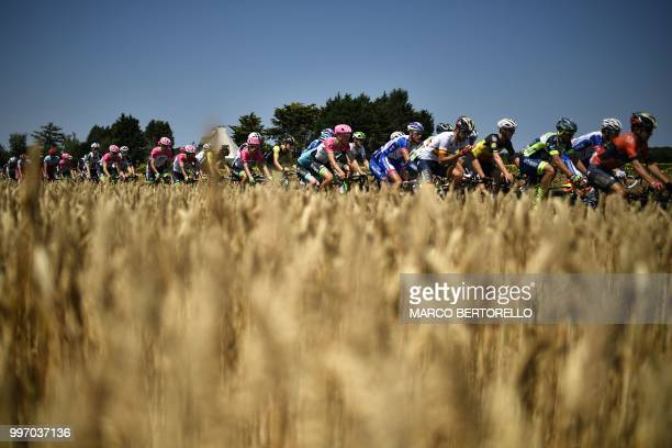 The pack rides past a wheat field during the sixth stage of the 105th edition of the Tour de France cycling race between Brest and Mur-de-Bretagne...