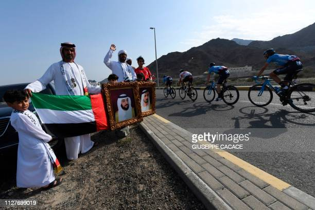 The pack rides past Emiratis carrying portraits of their President and Vice President during the fourth stage of the UAE cycling tour in Hatta on...
