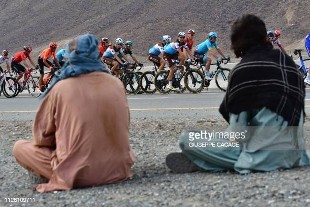 The pack rides past Emiratis during the fifth stage of the UAE tour from Sharjah to Khor Fakkan on February 28 2019