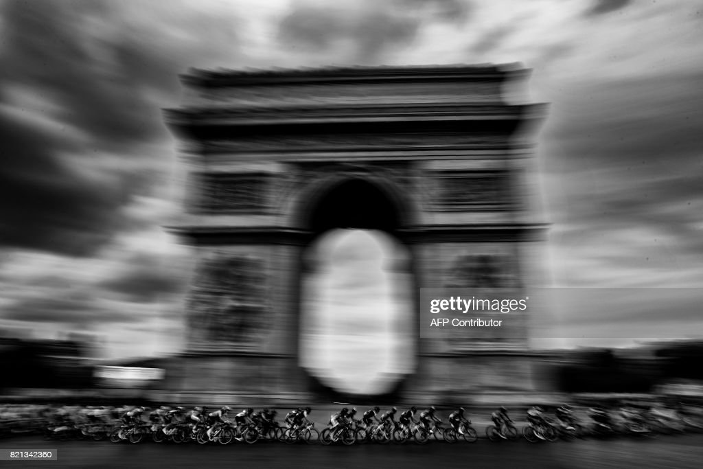 The pack rides past the Arc de Triomphe during the 103 km twenty-first and last stage of the 104th edition of the Tour de France cycling race on July 23, 2017 between Montgeron and Paris Champs-Elysees. /