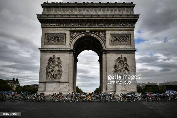 TOPSHOT The pack rides past the Arc de triomphe monument during the 21st and last stage of the 105th edition of the Tour de France cycling race...