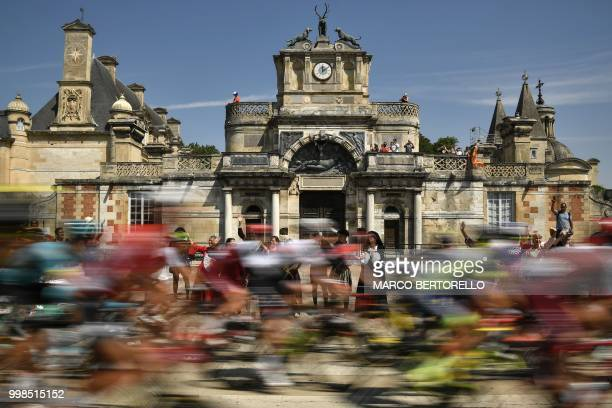 The pack rides past the entrance of the 16th Century Chateau d'Anet in Anet during the eighth stage of the 105th edition of the Tour de France...