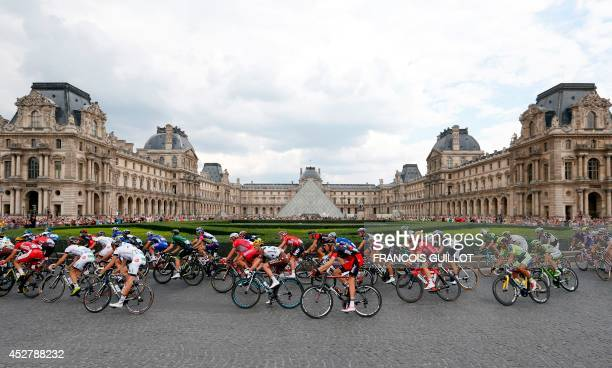 The pack rides past the Louvre Pyramid in Paris during the 137.5 km twenty-first and last stage of the 101st edition of the Tour de France cycling...