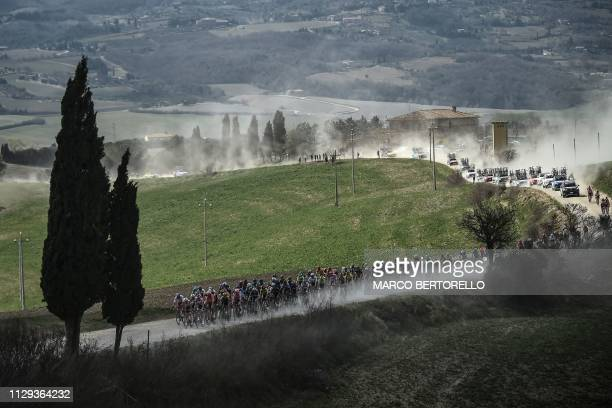 The pack rides through a dusty gravel road during the one-day classic cycling race Strade Bianche on March 9, 2019 around Siena, Tuscany.
