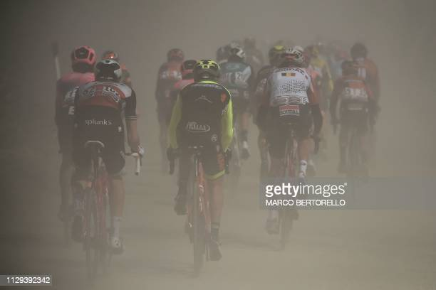 The pack rides through a dusty gravel road during the one-day classic cycling race Strade Bianche on March 9, 2019 in Siena, Tuscany.
