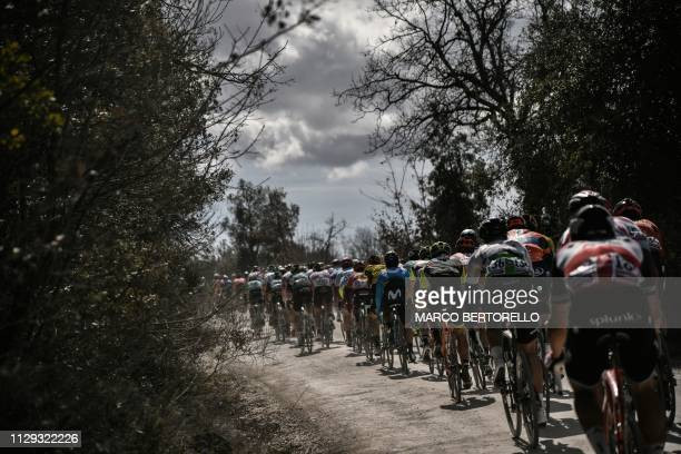 The pack rides through a dusty road during the one-day classic cycling race Strade Bianche on March 9, 2019 around Siena, Tuscany.