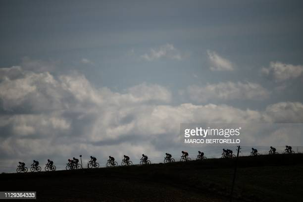 The pack rides through a gravel road during the one-day classic cycling race Strade Bianche on March 9, 2019 around Siena, Tuscany.